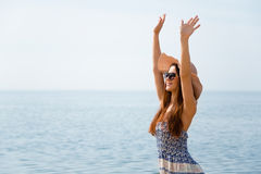 Girl with raised arms near the sea Royalty Free Stock Image