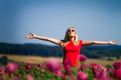Girl with raised arms outdoors. Teenage girl standing outdoors in a field of flowers with her arms outstretched and closed eyes Stock Image