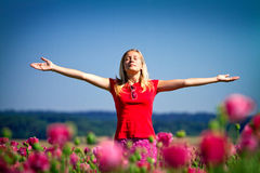 Girl with raised arms outdoors. Teenage girl standing outdoors in a field of flowers with her arms outstretched and closed eyes Royalty Free Stock Photos