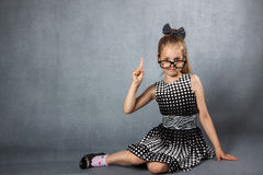 Girl with a raised finger. Smart girl with glasses Stock Image