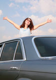 Girl with raised hands and car royalty free stock photography
