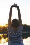The girl raised her arms up at sunset Stock Image
