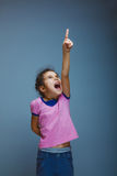 Girl raised her thumbs up shouting gray background Stock Images