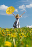 Girl with raised parasol in spring. Young girl with yellow parasol raised up on spring meadow stock images