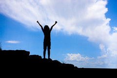 Girl raises arms in triumph. Stock Images