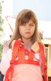 The girl raises heavy backpack Royalty Free Stock Image