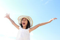 Girl raises her hands against blue sky Stock Image
