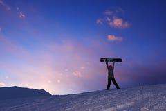 Girl raises snowboard up against  dark sunset sky Stock Photography