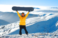 Girl raises snowboard up against panoramic winter mountain. S Royalty Free Stock Image