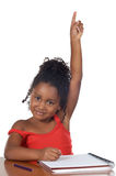 Girl raising hand. Cute girl with her hand raised at the school Royalty Free Stock Images