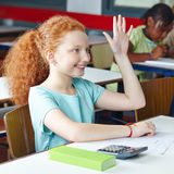 Girl raising hand in elementary Royalty Free Stock Image
