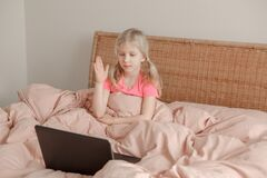 Girl raising hand and learning in virtual online school class. Kid sitting in bed and working on a laptop Internet at home. Child