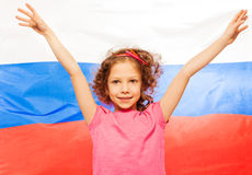 Girl raising her hands up, flag of Russia behind Royalty Free Stock Images