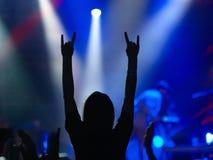 Girl raising up hands on rock concert Stock Photo