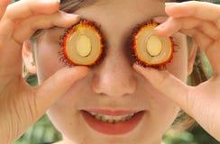 Girl with rambutan cut circle fruit Stock Photography