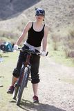 Girl in RAP bandanna by sport bicycle. In spring mountain Tien Shan Royalty Free Stock Photos