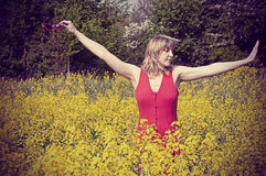 Girl in rapeseed field, dancing with joy. Royalty Free Stock Photography