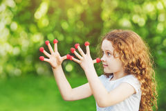 Girl with raspberry putting fingers to nose. Royalty Free Stock Images