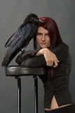 Girl with raven. Young woman with long red hair in black clothes with big raven on her hand on grey background Stock Photo