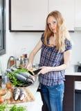Girl with raw  fish in fryingpan Stock Image