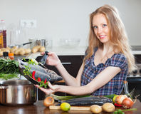 Girl with raw seabass fish in frying pan Stock Photography