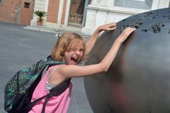 Girl reaches funnily loud in a piece of art in the city of Pisa, Italy. Girl with back bag reaches funnily loud in a piece of art on the Piazza dei Cavalieri in Royalty Free Stock Photo