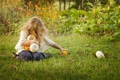 Girl reaching to pick up pumpkins Royalty Free Stock Image