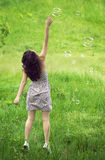The girl reaches out for soap bubbles Stock Image