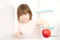 Girl reaching for apple. A young girl reaching for a large apple in a refrigerator stock photos