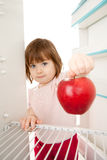 Girl reaching for apple Royalty Free Stock Photos