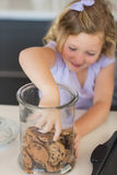 Girl reaching for cookies in jar Royalty Free Stock Images