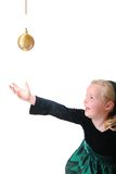 Girl reaching for ornament Royalty Free Stock Image