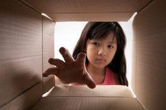 Girl reaching for things. Girl reaching for something inside the box stock image