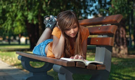 Girl read book. Relaxed girl read book in the park, FOCUS ON FACE Royalty Free Stock Photos