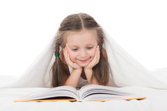 Girl read a book in bed. Under the blanket Royalty Free Stock Photos