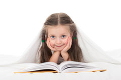 Girl read a book in bed. Under the blanket Stock Photo