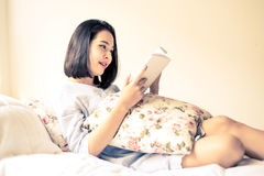 Girl read book on the bed. Vintage color tone. Young Asian girl reading white book on the white bed Stock Image