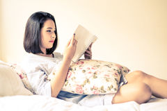 Girl read book on the bed. Vintage color tone. Young Asian girl reading white book on the white bed Royalty Free Stock Image