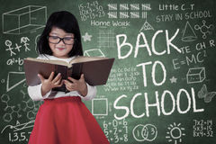 Girl read a book in front of blackboard Stock Images