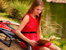 Girl read book near bicycle on river beach. Stock Photo