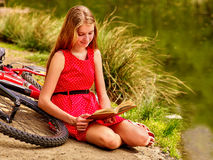 Girl read book near bicycle on river beach. Royalty Free Stock Photography