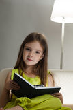 Girl read book on sofa Stock Images