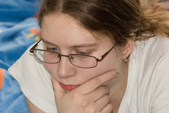 Girl reading. Closeup of the face of a young teenage girl as she reads or studies Stock Photography