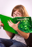 Girl Reading. A girl with glasses reading very engrossed in the book she is reading Royalty Free Stock Images