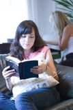 Girl reading. A brunette girl reading a book and a blonde girl playing the piano stock image