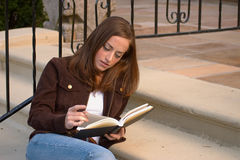 Girl Reading 3. Young woman reading/studying on steps Royalty Free Stock Images
