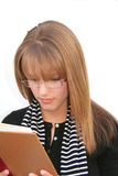 Girl reading. Beautiful blond girl, wearing glasses, reading. Isolated Stock Photo