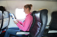 Girl reading in the airplane Royalty Free Stock Photo