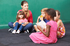 Girl reading aloud for children in kindergarten Royalty Free Stock Images