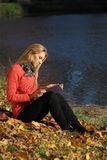Girl reading in autumn park Stock Photo